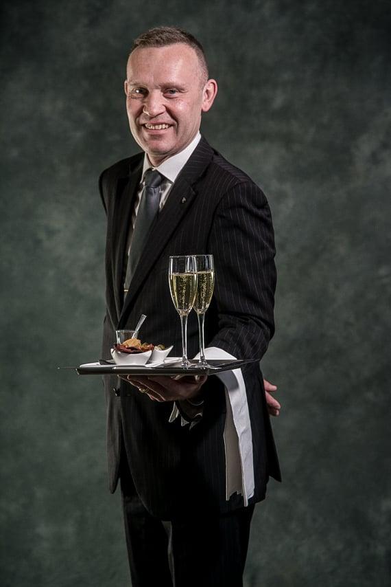 Serveur du restaurant, La Table De Mon Père avec une assiette d'amuses bouches et deux coupes de Champagne