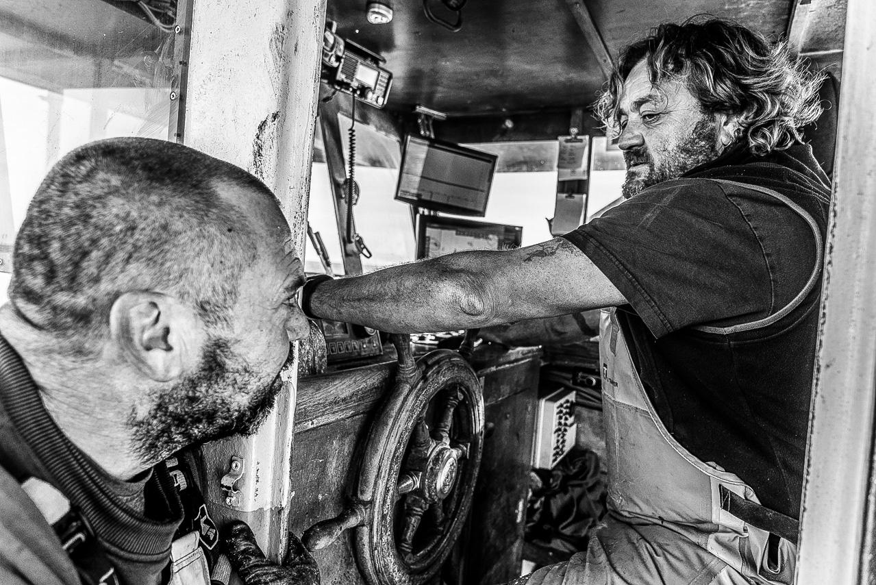 Echange de regards entre pêcheurs à la barre du chalutier