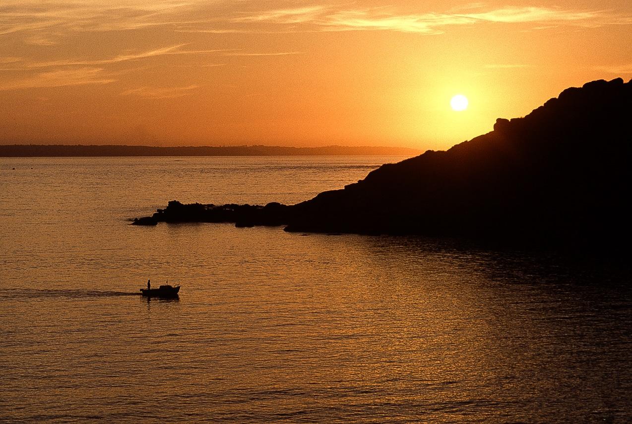 Pêcheur sur son bateau accompagné d'un magnifique coucher de soleil