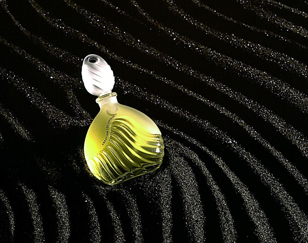 Bouteille de parfum Ted Lapidus sur sable noir