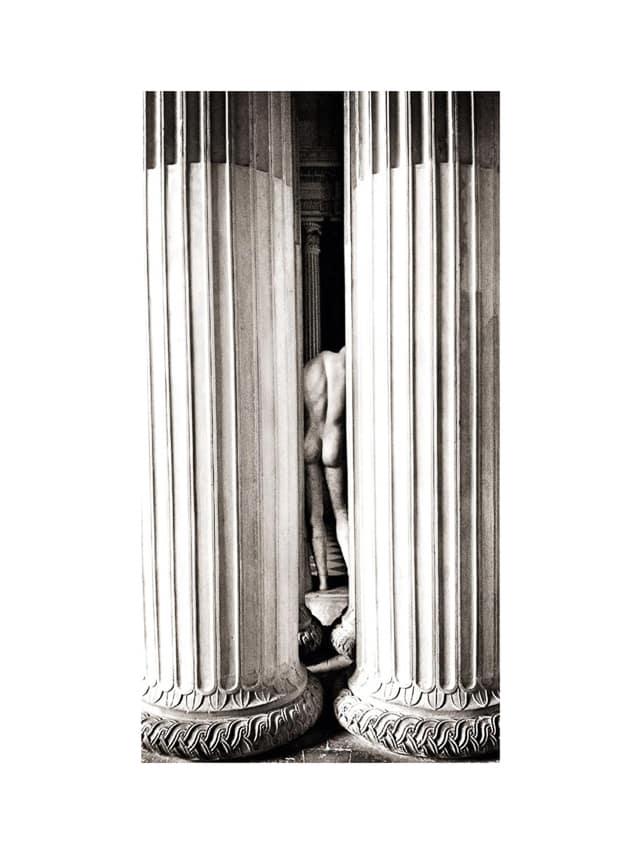 Homme nu de dos entre deux colonnes