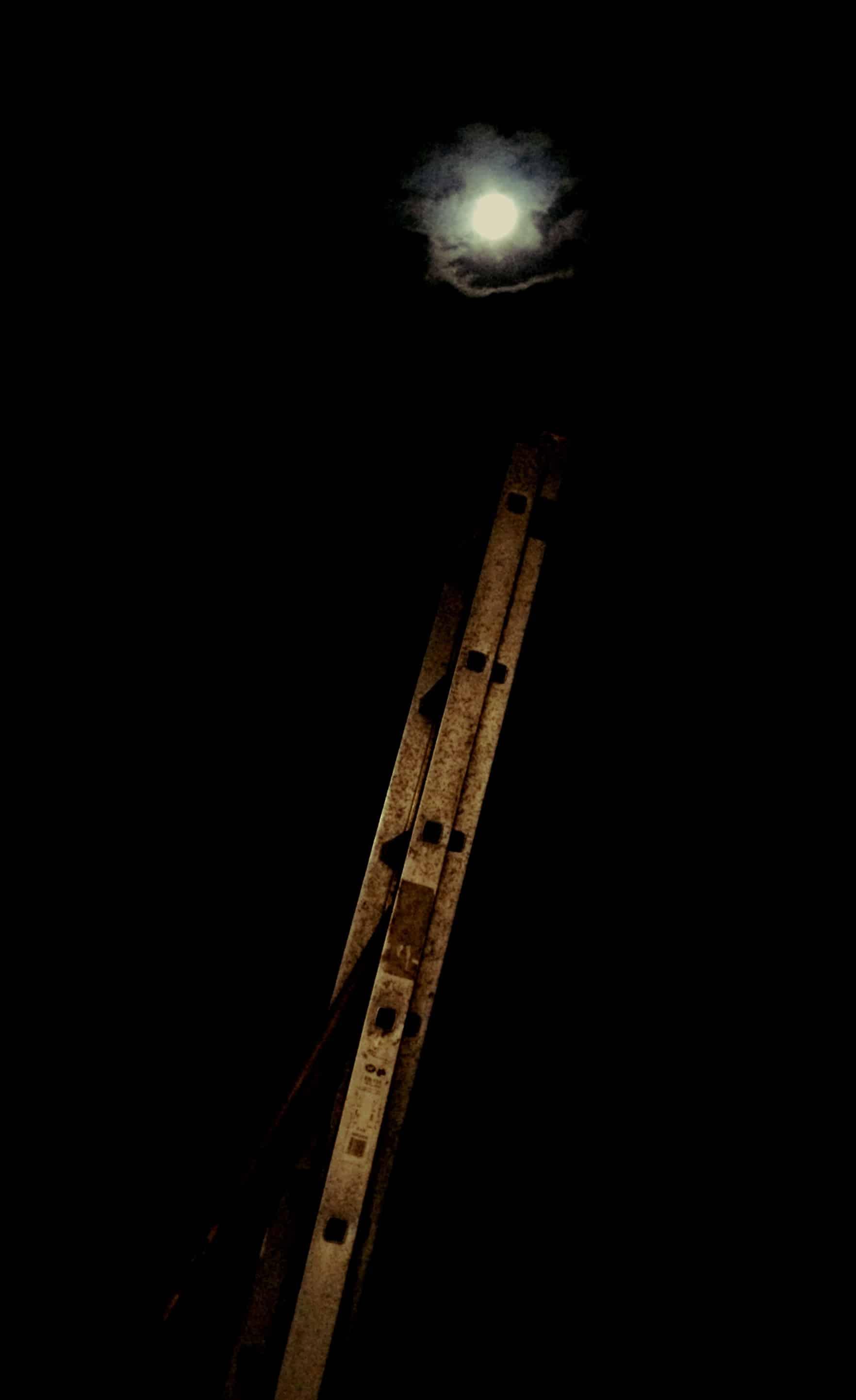 Un échelle et une lune en pleine nuit