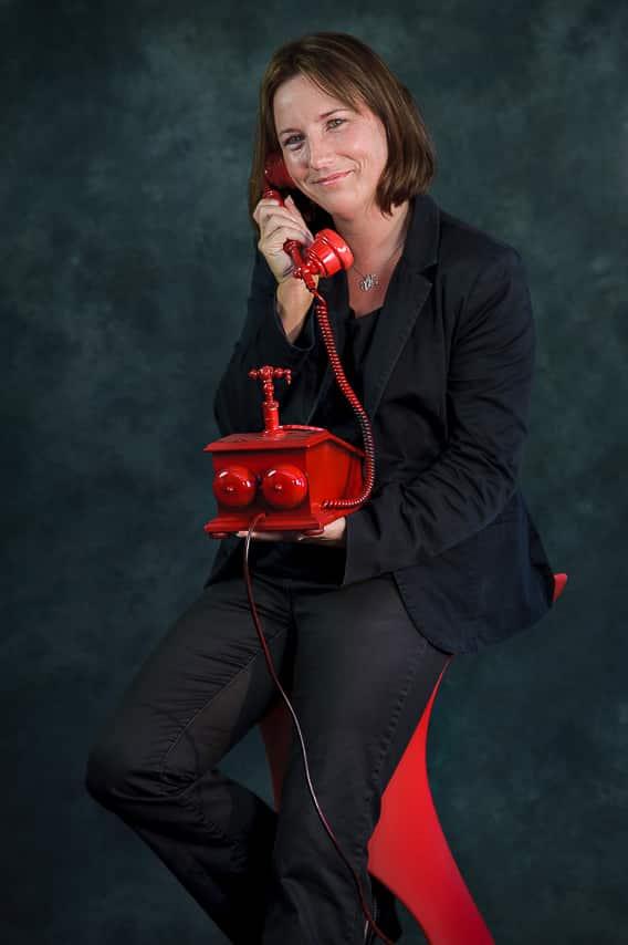 Portrait couleur d'une jeune femme avec un téléphone rouge à la main