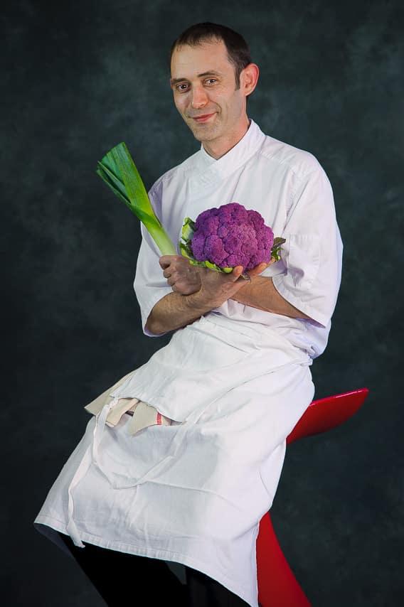 Portrait chef cuisinier avec chou et poireau dans les mains