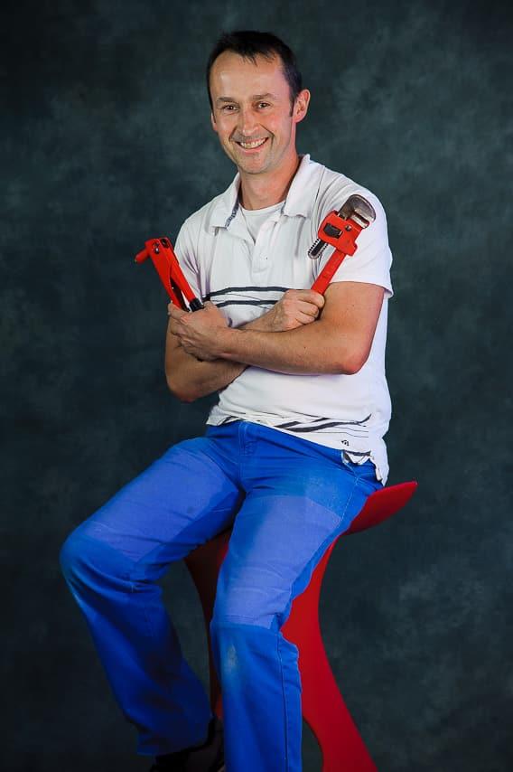 Portrait plombier avec des outils dans les mains