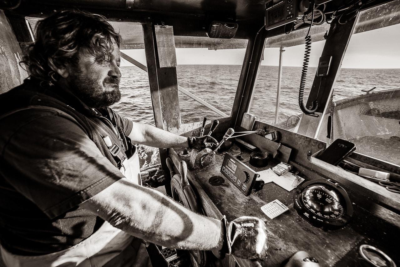 Pêcheur à la barre de son bateau