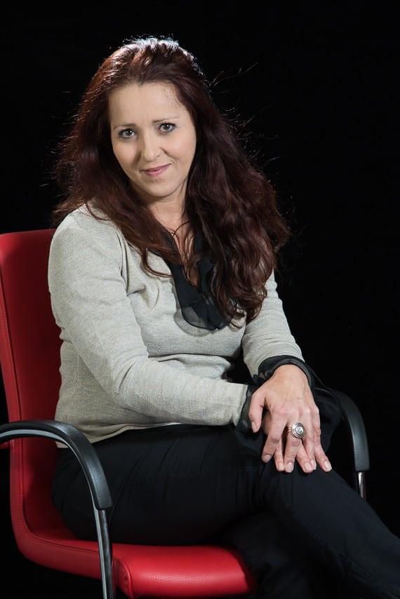 Portrait couleur d'une collaboratrice assise sur une chaise rouge